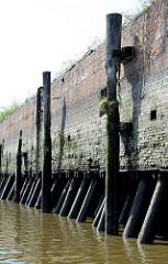 Kaimauer bei Ebbe im Hamburger Hafen; Streichdalben und Eisenleiter.  Bei Niedrigwasser zeigen sich die Baumstämme, die das Fundament der Kaianlage bilden.