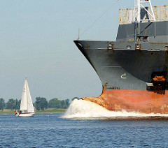 Schiffsbug eines Frachters / Frachtschiffs in Fahrt - kleines Segelschiff auf der Elbe.