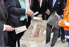 Grundsteinlegung Hauptgebäude TUHH - Die Ehrengäste nehmen die Kelle in die Hand und verstreichen den Zement für den Grundstein. Die kupferne Zeitkapsel liegt im Hohlraum des Grundsteins.