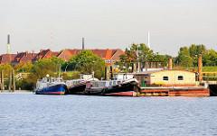 Bilder aus dem Hamburger Hafengebiet - Bilder vom Spreehafen - hinter dem Deich Wohnblocks in Hamburg Wilhelmsburg.