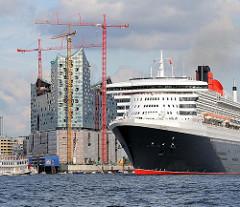 Das Kreuzfahrtschiff Queen Mary läuft aus dem Hamburger Hafen aus - im Hintergrund die Baustelle der Elbphilharmonie; hohe Baukräne.