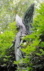 Bronzeengel zwischen Rhododendron - Figur mit Flügeln auf dem Friedhof Hamburg Ohlsdorf.
