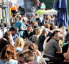 Sonnentag im Hamburger Stadtteil Sternschanze - Bewohner sitzen in der Sonne in Cafes und Restaurants auf der Strasse.