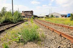 Gleisanlagen bei der Versmannstrasse in der Hafencity Hamburg - rostige Gleise, Lagerhäuser + Verwaltungsgebäude.