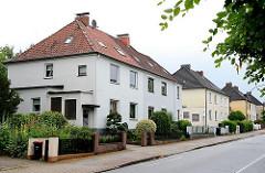 Nachkriegsarchitektur in Hamburg Langenbek - einstöckige Wohnblocks in einer Wohnstrasse.