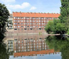 Wohnblock am Kanalufer spiegelt sich im Wasser - Bilder aus dem Hambuger Stadtteil Hamm.