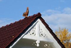 Dachfirst mit Schnitzerein und Hahn auf dem Dach in de Poppenbüttler Hauptstrasse.