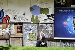 finden was man sucht - seitenstrasse mit graffiti und liebespaar mit werbeschild auf hamburg st. pauli.