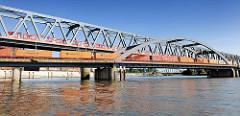 Eisenbahnbrücken über den Oberhafenkanal in der Hamburger Hafencity - ein S-Bahnzug und ein Güterzug mit Containern / Containerzug überqueren die Brücke. Im Hintergrund die Billhorner Brücke.