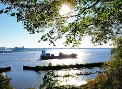 Containerfeeder auf der Elbe im Gegenlicht - Mühlenberger Yachthafen.