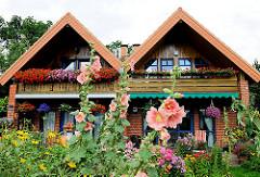 Doppelhaus in einer Seitenstrasse von Hamburg Steilshoop - blühende Geranien am Balkon - Stockrosen und Blumen im Vorgarten.