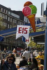 Eiscafe in der Eppendorfer Landstrasse - Fahne mit der Aufschrift Eis - Tische mit Gästen auf der Strasse.