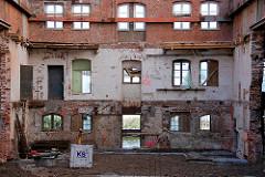 Das historische denkmalgeschützte Gebäude der Harburger Mühlenbetriebe wurde entkernt - durch die Fenster ist das Wasser des Westlichen Bahnhofskanals zu erkennen.