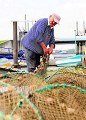 Fischfang im Hamburger Hafengebiet - die Reusen werden vom Fischer an Land ausgebreitet und geprüft.