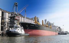 Ein Massengutfrachter legt ab - zwei Schlepper unterstützen das Schiff beim Ablegemanöver; im Hintergrund der Neuhöfer Kanal in Hamburg Wilhelmsburg, der früher mit dem Reiherstieg verbunden war.