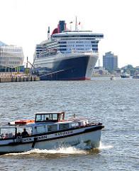 Blick über die Norderelbe zum Kreuzfahrtterminal Hamburg Hafencity - das Kreuzfahrtschiff Queen Mary hat am Kai festgemacht - im Vordergrund eine Hafenbarkasse mit Touristen.