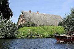 Strohdachhaus am Allermöher Deich - ein Fahrradfahrer fährt auf der Deichstrasse - auf dem Fluss der Bug eines Motorboots.