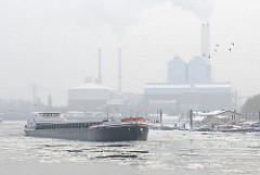 Das Binnenschiff NIEDERSACHSEN fährt durch das eisbedeckte Wasser der Billwerder Bucht - das Schiff hat Kohle für das Kraftwerk Tiefstack gebracht, das im Hintergrund im Dunst zu erkennen ist.