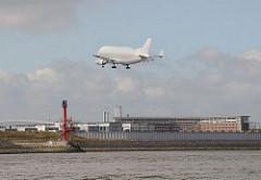 Airbuswerk F inkenwerder Beluga Transportflugzeug über der Elbe.