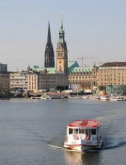 Alsterdampfer auf der Binnenalster - das Alsterschiff kommt vom Anleger am Jungfernstieg und fährt Richtung Aussenalster. Im Hintergrund die Reesendammbrücke - dahinter der Rathausturm und der Kirchturm der St. Nikolaikirche.