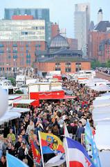 Sonntag früh in Hamburg - der Altonaer Fischmarkt als Sehenswürdigkeit der Hansestadt - dicht gedrängt gehen die Besucher zwischen den Marktständen - im Hintergrund die historische Fischauktionshalle und Industriearchitektur / Büroarchitektur in der