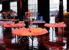 Festdekoration auf den Tischen in der Fischauktíonshalle, die vom Hochwasser erreicht wurde - im Hintergrund die Elbe und ein Schiff im Dock von Blohm + Voss.