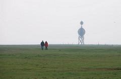 ehem. Kugelbake, hölzerne Sichtmarke - Ostbake auf Neuwerk - Spaziergänger auf einer Wiese - Dunst über der Nordsee.