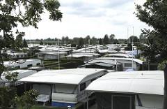 Campingplatz am  Oortkatener See - Campingwagen stehen dicht an dicht auf der Campinganlage.