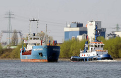Das Küstenmotorschiff WILSON RUHR fährt in den Reiherstieg ein - der Kümo wird von einem Hafenschlepper überholt. Im Hintergrund Industriegebäude in Hamburg Wilhelmsburg.