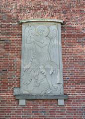 Steinrelief mit dem Erzengel Michael, der den Drachen bekämft.