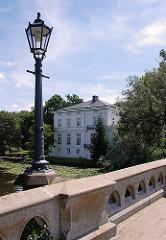 Historische Laterne auf der Feenteichbrücke - Gästehaus des Senats am Feenteich im Hintergrund.