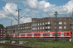 Wohnblocks an der S-Bahnstrecke - Hamburg Veddel, fahrender Zug vor den Fenstern der Wohnungen.