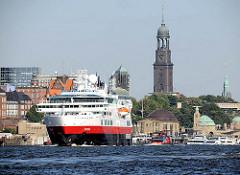 Das Kreuzfahrtschiff Fram verlässt den Hamburger Hafen - rechts die St. Pauli Landungsbrücken und die Hamburger St. Michaeliskirche.