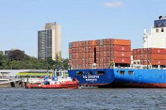 Mit Containern hochbeladenes Heck des Frachters HS CHOPIN, ein Hafenschlepper dirigiert das Schiff an Seinen Liegeplatz im Hamburger Hafen.