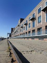 Zu Bürogebäuden umgebauten Speicher am Ufer des Altonaer Hafens. Im Vordergrund eine Laufschiene eines Halbportalkrans.