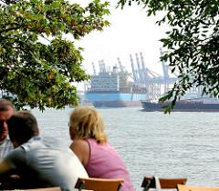 Café an der Elbe in Hamburg Othmarschen, die Gäste sitzen an Tischen am Fluss - im Hintergrund läuft ein Containerschiff in den Hamburger Hafen ein; Containerkräne vom Waltershofer Hafen.