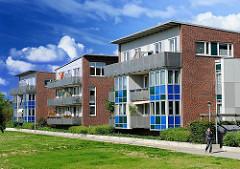 Neubauwohnungen in Hamburg Neuallermöhe - mehrstöckige Wohnblocks mit Balkons; Wiese am Weg.