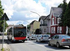 Bus der HVV in der Rahlstedter Amststrasse - PKW Verkehr und farbige Einzelhäuser am Strassenrand.