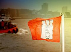 Flagge der Freien und Hansestadt Hamburg flattert im Wind - Silhouette der Stadt - Foto aus dem Hamburger Hafen / Elbe.