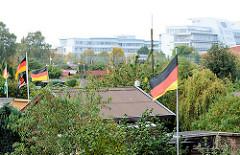 Kleingarten im Hamburger Stadtteil Barmbek Nord - Gartenlauben, im Hintergrund moderne Bürogebäude.