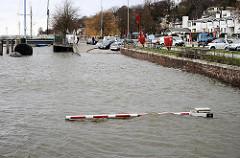 Ein Parkplatz am Museumshafen von Oevelgönne in Hamburg Othrmarschen steht unter Wasser; nur noch die Schranke ist zu erkennen.