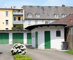 Garagen mit grünen Holztüren - halbrunder Schuppen - Wohnblocks im Hintergrund, Nachkriegsarchitektur.