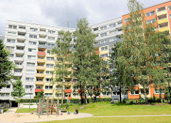 Spielplatz und Hochhäuser in Hamburg Steilshoop - modernisierte Wohnhäuser mit bunter Fassade und Balkon.