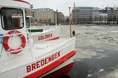 Winter auf der Hamburger Alster - die Fahrgastschiffe haben Winterpause - die Binnenalster ist mit Eis bedeckt. Im Hintergrund der Ballindamm und das Alstertor im Hamburger Stadtteil Altstadt.