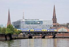 Blick vom Oberhafenkanal auf die Oberhafenbrücke - im Hintergrund ein modernes Bürogebäude am Deichtorplatz und die Kirchtürme der Hamburger Hauptkirchen St. Petri und St. Jacobi Kirche.