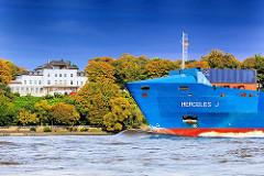 Schiffsbug eines Containerfeeders vor herbstlichen Bäumen am Elbhang von Hamburg Othmarschen.