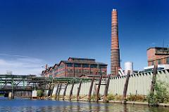 Industriegebäude am Müggenburger Kanal in Hamburg Veddel, Bezirk Mitte. Ziegelarchitektur - hoher Schornstein, Kaimauer.