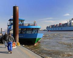 Fähranleger Teufelsbrück - die Hafenfähre Waltershof wird gleich ablegen - Fahrgäste sprinten auf dem Anleger zum Schiff - Im Hintergrund ein Containerfrachter Richtung Hafen.