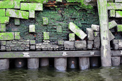 Alte, teilweise zerstörte Kaimauer im Hamburger Hafen; bei Niedrigwasser zeigen sich die Baumstämme, die das Fundament der Kaianlage bilden.