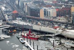 Blick auf die Baustelle Uferpromenade / Hafenpromenade am Sportboothafen in der Hamburger Neustadt; Hochbahnviadukt am Baumwall - rotes Feuerschiff im Eis.
